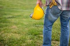 Man den hållande konstruktionshjälmen med handskar i fack Arkivbild