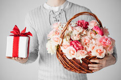 Man den hållande korgen som är full av blommor och gåvaasken Royaltyfria Bilder