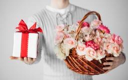 Man den hållande korgen som är full av blommor och gåvaasken Arkivbild