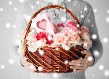 Man den hållande korgen som är full av blommor och vykortet Fotografering för Bildbyråer