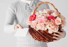 Man den hållande korgen som är full av blommor och vykortet Arkivbild