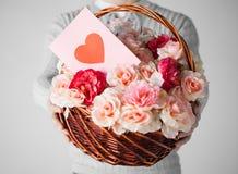 Man den hållande korgen som är full av blommor och vykortet Arkivbilder