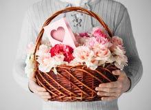 Man den hållande korgen som är full av blommor och vykortet Arkivfoto