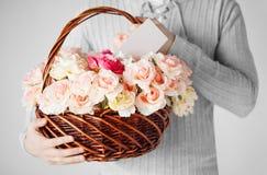 Man den hållande korgen som är full av blommor och vykortet royaltyfria foton