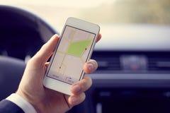 Man den hållande mobilen med översiktsgps-navigering som tonas Royaltyfri Foto