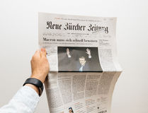 Man den hållande Neue Burcher Zeitung tidningen med Emmanuel Macron Arkivbild