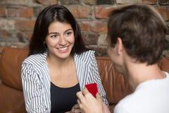Man den hållande röda asken med förlovningsring- och danandeförslag fotografering för bildbyråer