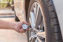 Man den hållande tryckmätaren och att kontrollera lufttryck av bilen Royaltyfri Bild