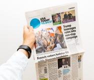 Man den hållande USA Today tidningen med Emmanuel Macron på första PA Fotografering för Bildbyråer