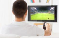 Man den hållande ögonen på fotbollleken på tv hemma från baksida Royaltyfria Foton
