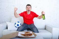 Man den hållande ögonen på fotbollleken på tv i lagärmlös tröja som firar galen lycklig banhoppning för mål på soffan Arkivfoton