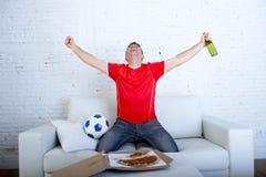 Man den hållande ögonen på fotbollleken på tv i lagärmlös tröja som firar galen lycklig banhoppning för mål på soffan Royaltyfria Foton