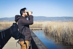 Man den hållande ögonen på naturen med kikare, i en wood bro Royaltyfri Bild