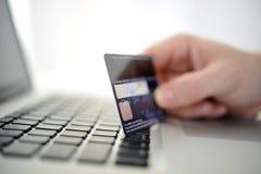 Man den hållande kreditkorten i handonline-shopping och bankrörelsen Arkivbild