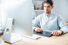 Man den märkes- funktionsdugliga användande datoren och den grafiska minnestavlan på arbetsplatsen Arkivfoton