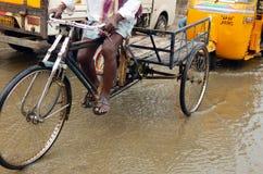 Man den ritttrehjulingen eller rickshawen i översvämmad väg för regnvatten Royaltyfria Bilder