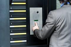 Man den skrivande in säkerhetskoden för att låsa dörren upp Royaltyfri Bild