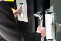 Man den skrivande in säkerhetskoden för att låsa dörren upp Fotografering för Bildbyråer