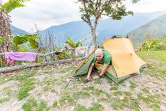 Man den turist- fotvandrareuppvaknandet som ut får tältet som campar, Boliv Arkivbild