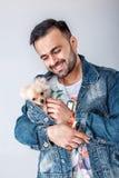 Man in denim jacket holds pomeranian dog. stock photos