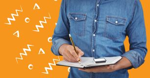Man denim shirt mid section with notebook against orange background with white patterns. Digital composite of Man denim shirt mid section with notebook against Stock Image