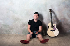 Man in denim shorts sitting next to a guitar on the wall background in style grunge, music, musician, hobby, lifestyle, hobby Royalty Free Stock Photography