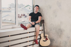 Man in denim shorts sitting next to a guitar on the wall background in style grunge, music, musician, hobby, lifestyle, hobby Royalty Free Stock Photos