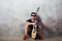 Man in denim shorts sitting next to a guitar on the wall background in style grunge, music, musician, hobby, lifestyle, hobby Stock Photo