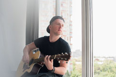 Man in denim shorts sitting with to the window with his guitar music, musician, hobby, lifestyle, hobby Stock Image