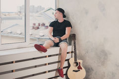 Man in denim shorts sitting with to the window with his guitar music, musician, hobby, lifestyle, hobby Stock Photos