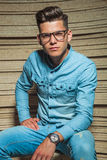 Man in denim wearing glasses sitting and posing. In wooden studio Stock Photography