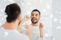 Man with dental floss cleaning teeth at bathroom Stock Image