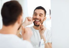 Man with dental floss cleaning teeth at bathroom Stock Photography