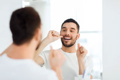 Man with dental floss cleaning teeth at bathroom Royalty Free Stock Photo