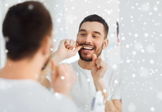 Man with dental floss cleaning teeth at bathroom Royalty Free Stock Photos