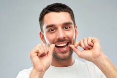 Man with dental floss cleaning teeth over gray Royalty Free Stock Images