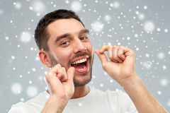 Man with dental floss cleaning teeth over snow Stock Photography