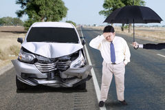 Man with dented car and umbrella Royalty Free Stock Images