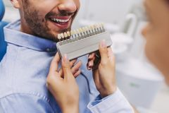 Man in dentist chair choosing tooth implants royalty free stock photography