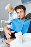 Man at dentist reaching for cup of water Royalty Free Stock Photos