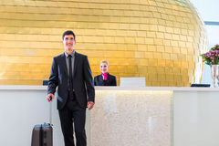 Man departing on business trip at hotel reception Royalty Free Stock Photos