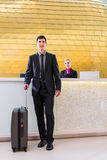 Man departing on business trip at hotel reception Royalty Free Stock Images