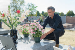 Man depositing flowers on tomb Royalty Free Stock Photo