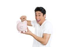 Man depositing money into piggy bank Stock Images