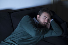 Man depressed thinking lying on the couch Stock Photo
