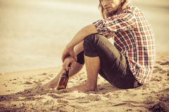 Man depressed with wine bottle sitting on beach outdoor Royalty Free Stock Image