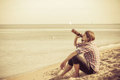 Man depressed with wine bottle sitting on beach outdoor Royalty Free Stock Images