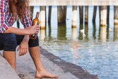 Man depressed with wine bottle sitting on beach outdoor Royalty Free Stock Photo