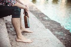 Man depressed with wine bottle sitting on beach outdoor Stock Photo