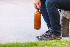 Man depressed with wine bottle sitting on bench outdoor Stock Images